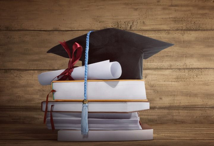 graduation-cap-with-graduation-paper-on-a-stack-of-book-picture-id654454466